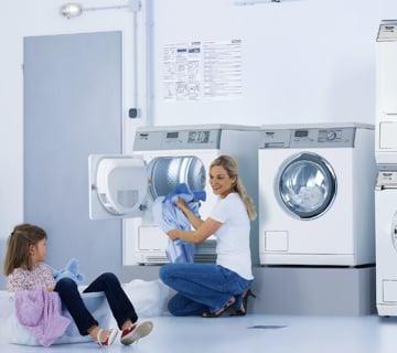 Frau belädt Waschmaschine - Gewerbegeräte von Elha Service