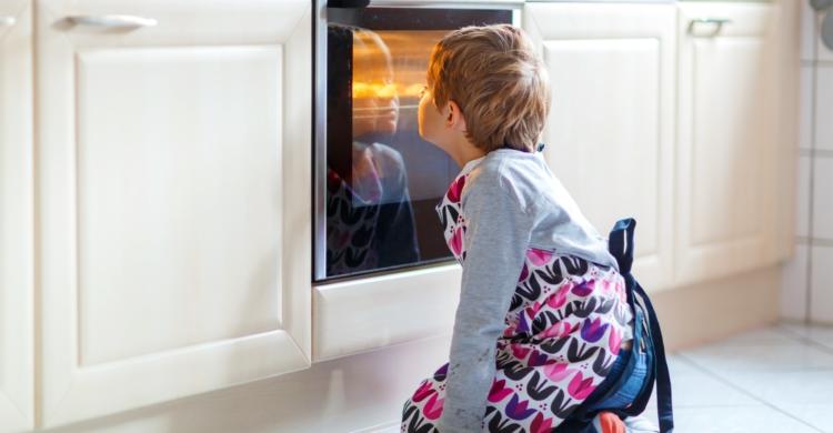 Kinder schaut in Ofen herein - schützen Sie Ihre Kinder vor Gefahren in der Küche