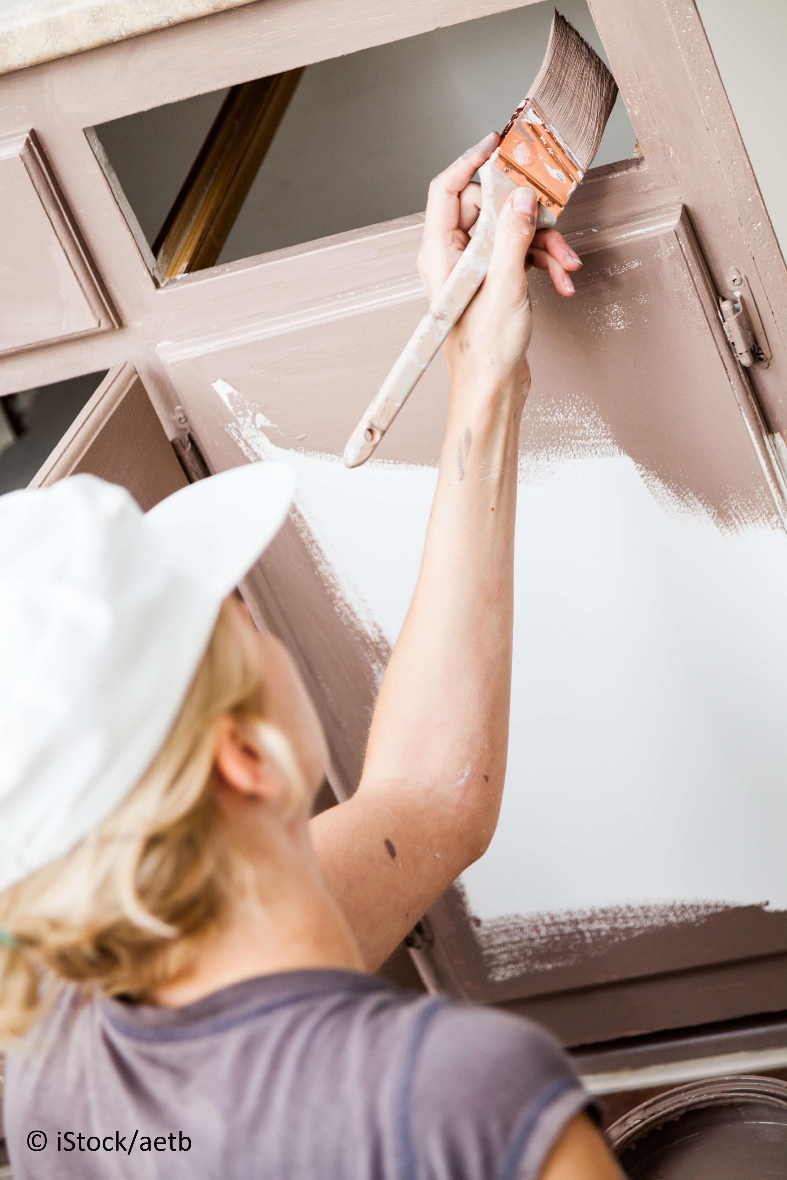 Frau lackiert Küchenfront neu