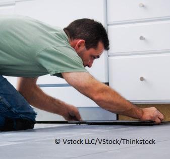 Mann erneuert Küchenfront und misst sie ab