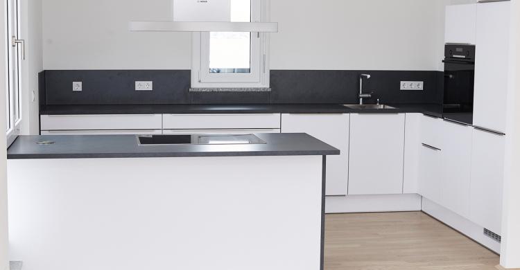 Moderne weiße Küche mit Schieferarbeitsplatten