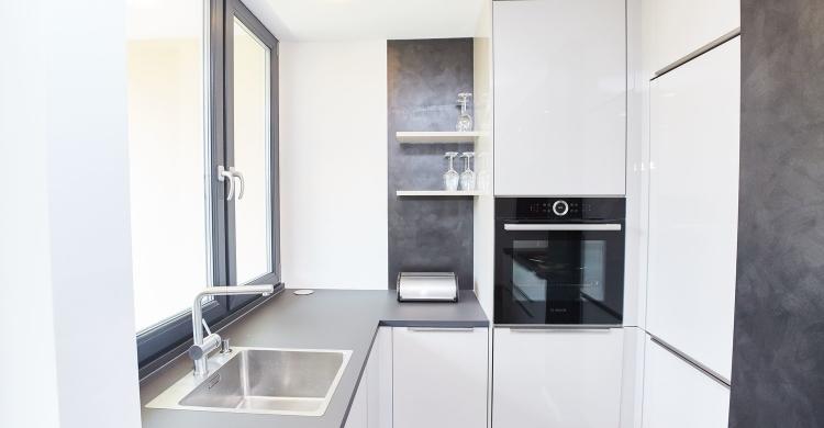 Die hellen Fronten und die dunkle Arbeitsplatte bilden einen angenehmen Kontrast in der Designer Küche mit Kochinsel
