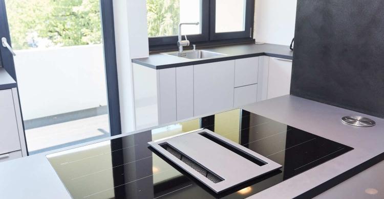Die Kochinsel Der Designer Küche Ist Mit Einem Modernen Induktionskochfeld  Ausgestattet.