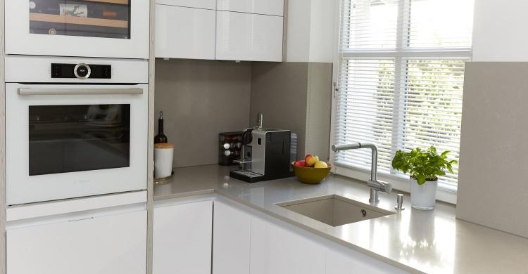 Die hier gezeigteweiße Küche, helle Arbeitsplatteüberzeugt durch ihre klare Linienführung.