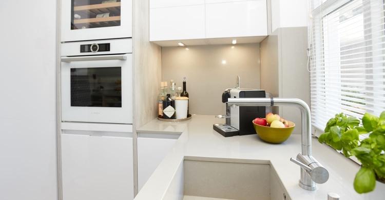 Durch das aparte Spülbecken in der weißen Küche, helle Arbeitsplatte wirkt das Gesamtkonzept sehr stimmig und in sich ruhend.