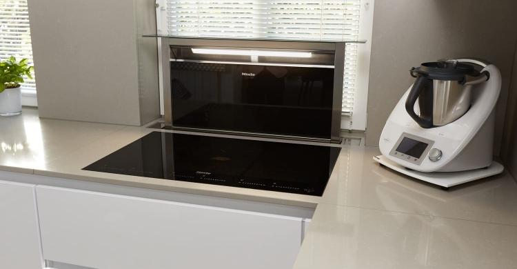 Dieweiße Küche, helle Arbeitsplattepunktet mit innovativen technischen Lösungen. Das großzügige Induktionskochfeld Miele KM63671 mit flächenbündigem Einbau sieht elegant aus und bietet ein Maximum an Komfort.