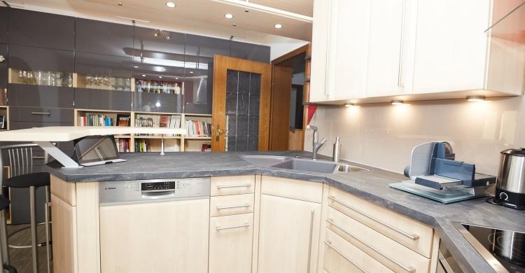 Der vorherige offene Hängeschrank wurde durch drei Regalbretter ersetzt, die die helle Holzküche ergänzen.
