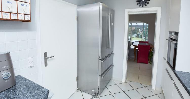 Gestaltung einer Küche mit Arbeitsplatte aus Naturstein und matten Küchenfronten-kühlschrank