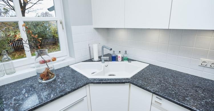 Gestaltung einer Küche mit Arbeitsplatte aus Naturstein und matten Küchenfronten-eckspüle