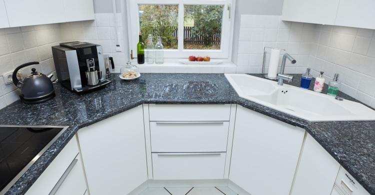 Gestaltung einer Küche mit Arbeitsplatte aus Naturstein und matten Küchenfronten-fenster