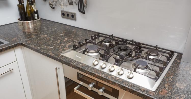 küchenfronten-aus-glas-und-natursteinplatte-gaskochfeld